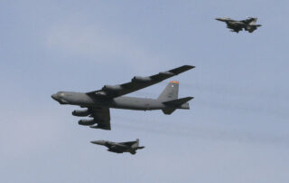 B-52 bomber plane escorted by fighter jets